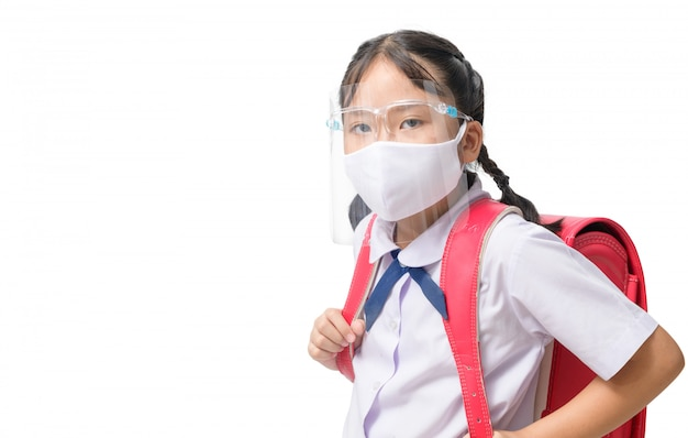 Aluna asiática usa escudo facial e máscara carrega saco de escola isolado