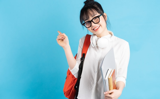 Aluna asiática usando mochila nas costas, segurando um smartphone, pescoço usando fones de ouvido sem fio, segurando um copo de papel