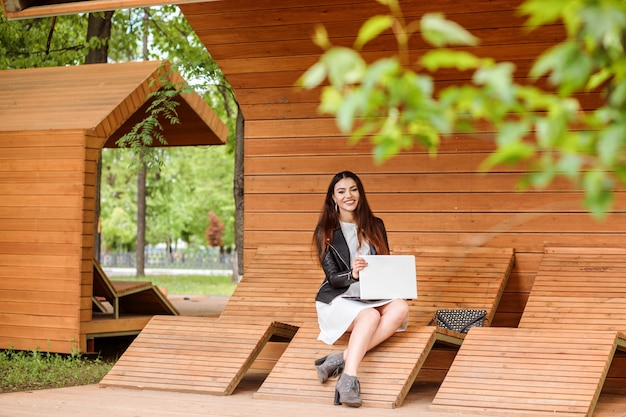 Aluna atraente está trabalhando ou estudando em seu laptop ao ar livre no parque no verão ou na primavera. mulher elegante está vestida com uma jaqueta de couro e um vestido branco, sentada no moderno banco de madeira