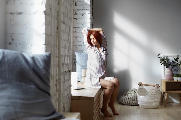 Aluna bonita com cabelo ruivo sentada no parapeito da janela e esticando os braços de manhã cedo após acordar, assistindo ao tutorial de ioga na internet usando um notebook, sorrindo amplamente