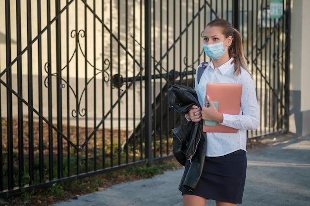 Aluna bonita com uma máscara médica protetora está andando pela rua da cidade para a escola