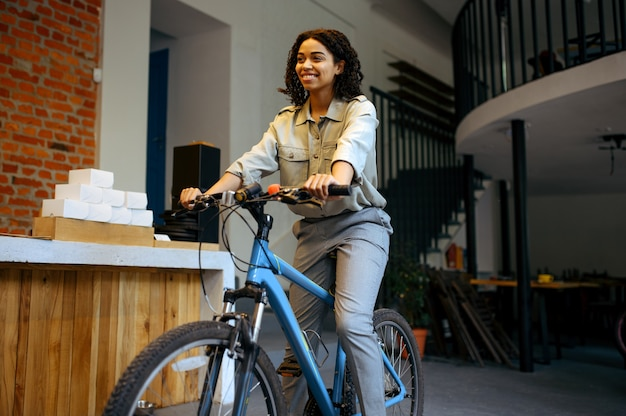 Aluna bonita posa de bicicleta no café. mulher aprendendo um assunto em cafeteria, educação e comida. menina estudando na cafeteria do campus