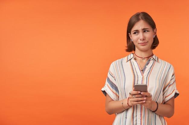 Aluna bonita segurando um smartphone e não acreditando no que viu. vestindo camisa listrada, aparelho dentário e pulseiras. assistindo à esquerda no espaço da cópia contra a parede laranja