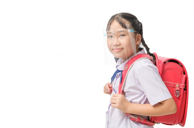 Aluna bonito usando escudo facial e carrega a mochila para ir à escola isolada