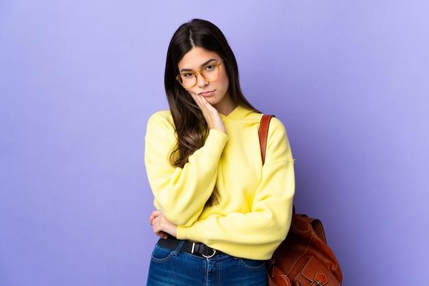 Aluna brasileira adolescente sobre fundo roxo isolado infeliz e frustrada