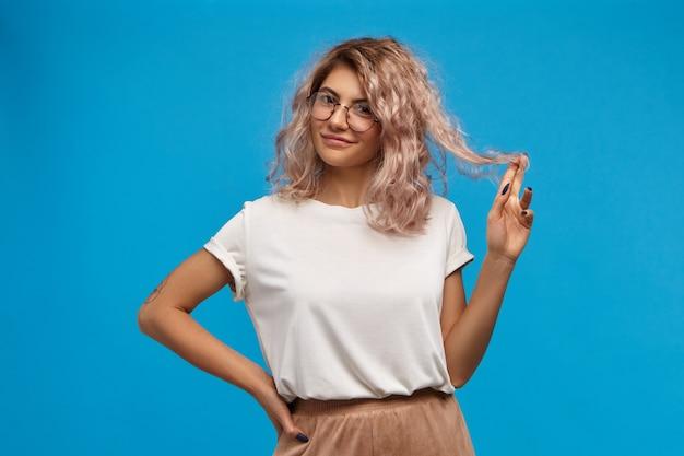 Aluna brincalhona com uma camiseta branca enorme e óculos redondos, com um sorriso sedutor, torcendo o cabelo rosado no dedo. pessoas, estilo de vida, feminilidade