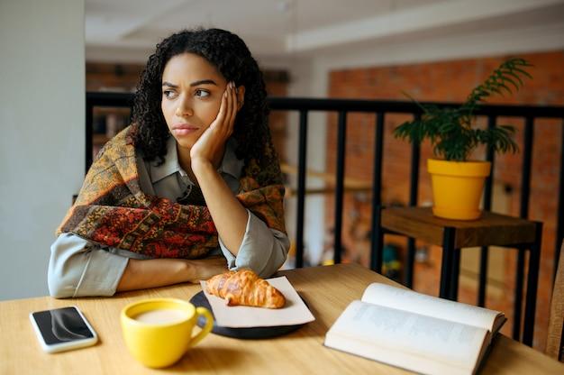 Aluna cansada à mesa no café. mulher aprendendo um assunto em cafeteria, educação e comida. menina estudando na cafeteria do campus