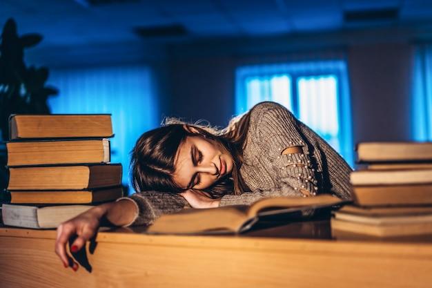 Aluna cansada à noite dorme na biblioteca na recepção com livros. ensino e preparação para exames
