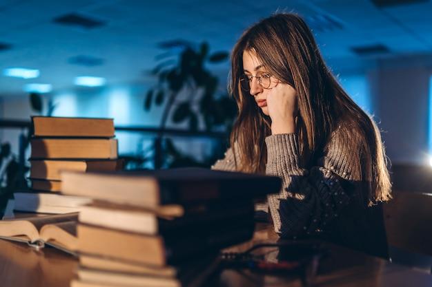 Aluna cansada à noite sentado encostado no braço na biblioteca na recepção com livros. ensino e preparação para exames.