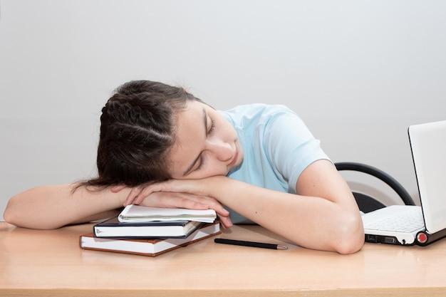 Aluna cansada com livros e laptop dorme na mesa.