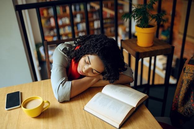 Aluna cansada dorme à mesa no café. mulher aprendendo um assunto em cafeteria, educação e comida. menina estudando na cafeteria do campus