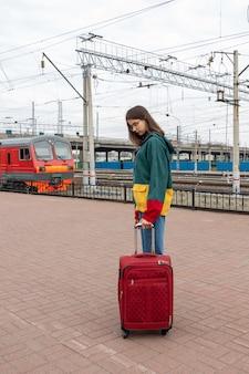 Aluna caucasiana com roupas brilhantes com uma mala para o trem elétrico na estação. menina com uma mala na estação ferroviária. uma viagem de férias para alunos.