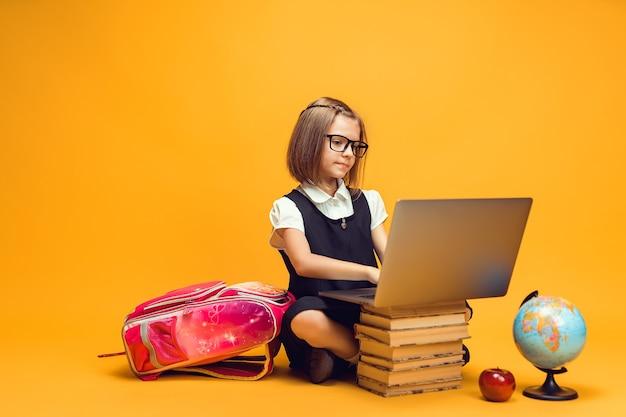 Aluna caucasiana de corpo inteiro sentada atrás de uma pilha de livros, trabalhando na educação de crianças em laptop