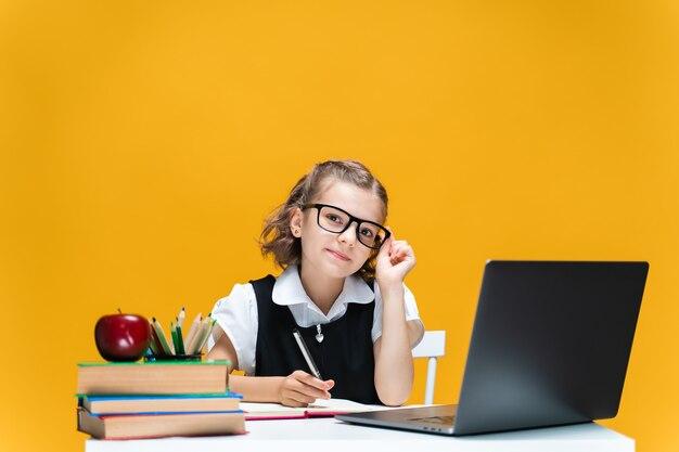 Aluna caucasiana de óculos sentada em frente ao laptop durante a aula on-line, aprendizagem em escolas distantes