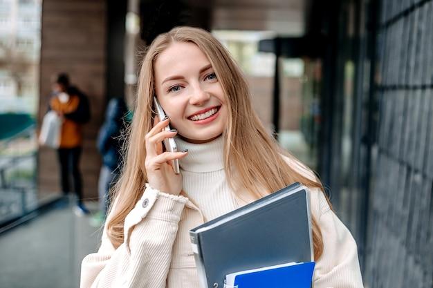 Aluna caucasiana falando em um telefone celular segurando pastas, livros, cadernos, sorrisos, em um prédio moderno de universidade