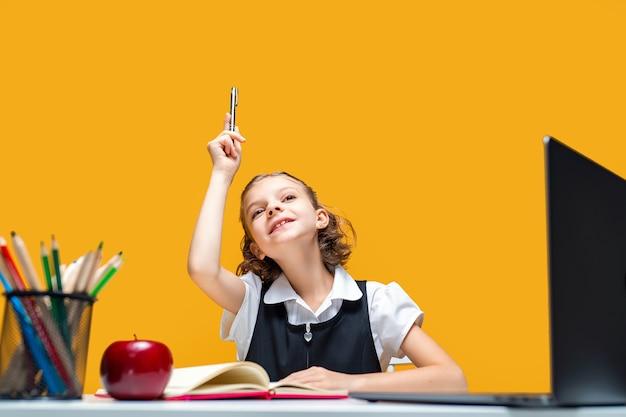 Aluna caucasiana levanta a mão com uma caneta sentada no laptop em uma escola distante, aprendendo