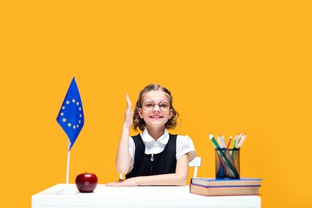 Aluna caucasiana levantando a mão sentada na mesa durante a aula, aula de inglês, bandeira da europa