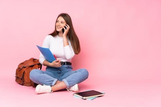 Aluna caucasiano estudante sentado no chão isolado na parede rosa, mantendo uma conversa com o telefone móvel