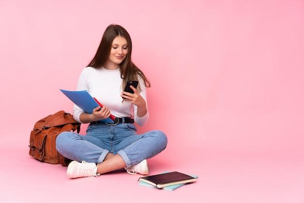 Aluna caucasiano estudante sentado no chão isolado no rosa, enviando uma mensagem com o celular