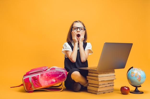Aluna chocada de corpo inteiro sentada atrás de uma pilha de livros com o pc olhando para a câmera educação infantil