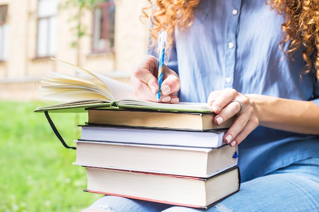 Aluna com cabelo longo encaracolado escreve em um caderno sobre uma pilha de livros