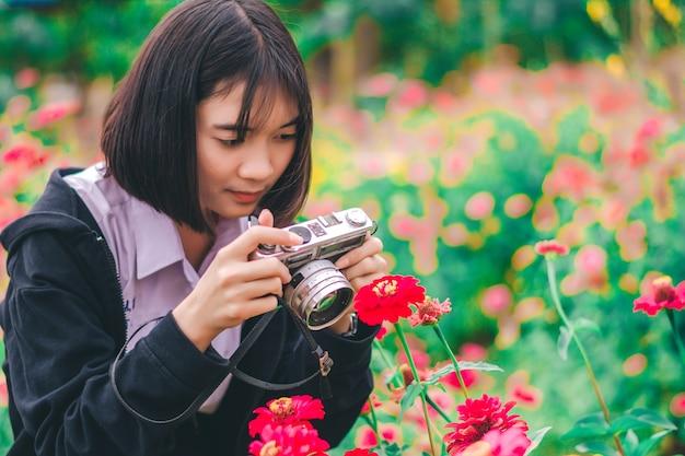 Aluna com câmera vintage no jardim de flores