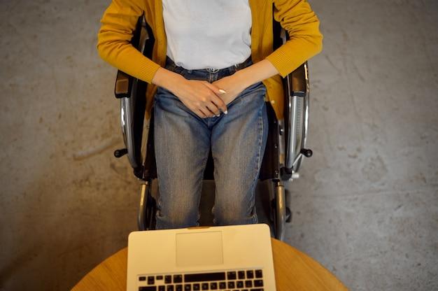 Aluna com deficiência em cadeira de rodas usando laptop