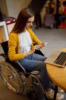 Aluna com deficiência em cadeira de rodas usando telefone