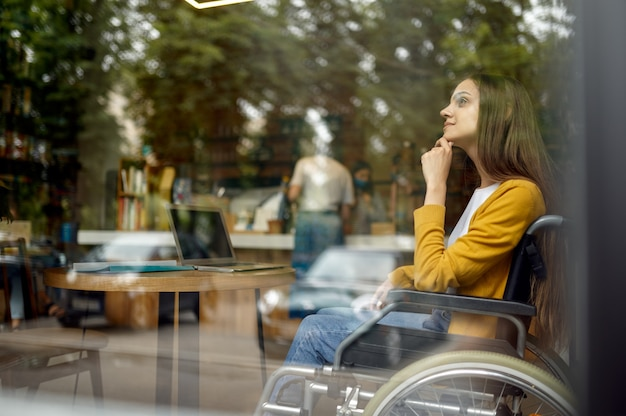 Aluna com deficiência em cadeira de rodas, vista de janela, deficiência, estante e interior da biblioteca da universidade no fundo. jovem com deficiência estudando na faculdade, pessoas paralíticas obtêm conhecimento