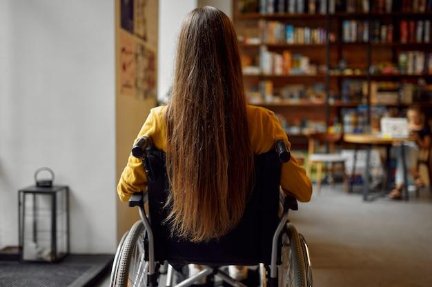Aluna com deficiência em cadeira de rodas, vista traseira, deficiência, estante e interior da biblioteca da universidade no fundo. jovem com deficiência estudando na faculdade, pessoas paralíticas obtêm conhecimento