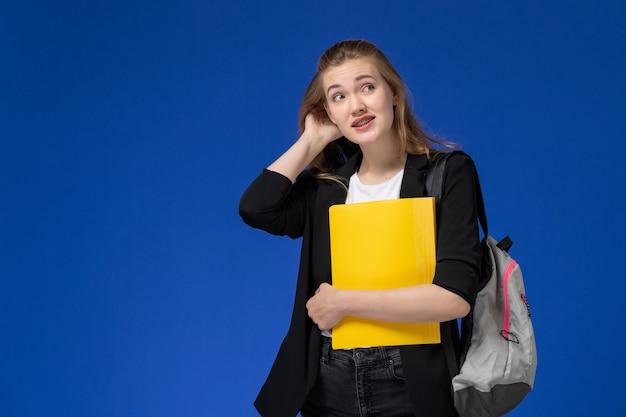 Aluna com jaqueta preta e mochila segurando arquivos amarelos na parede azul-claro.