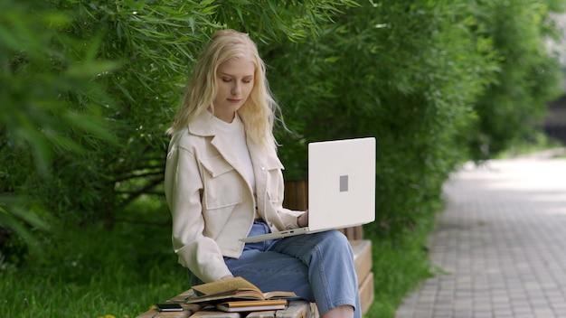 Aluna com laptop e livros se senta em um banco do parque. uma jovem folheia livros e imprime em um laptop contra um fundo de árvores verdes. dias de estudo ao ar livre. 4k uhd
