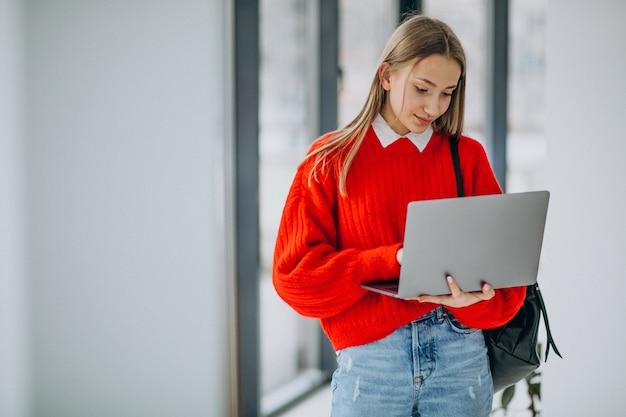 Aluna com laptop em pé junto à janela no corredor