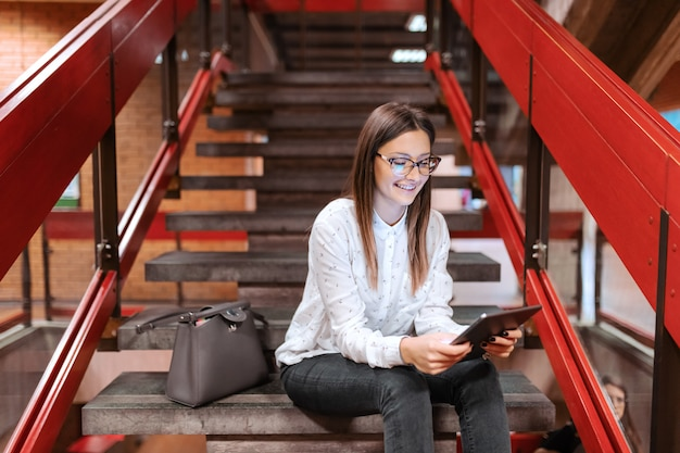 Aluna com óculos e cabelos castanhos usando tablet enquanto está sentado na escada