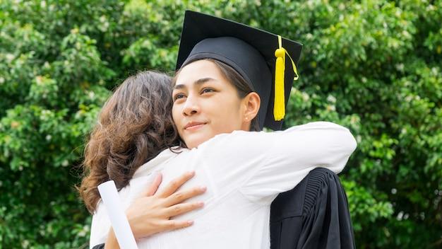 Aluna com os vestidos de formatura e chapéu abraçar os pais na cerimônia de parabéns.