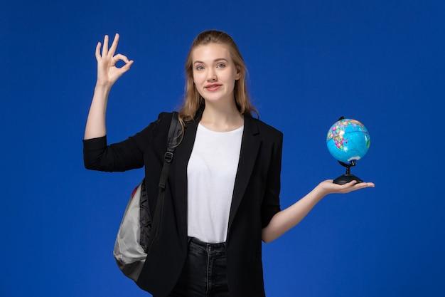 Aluna com uma jaqueta preta e uma mochila segurando um globo na parede azul-claro.