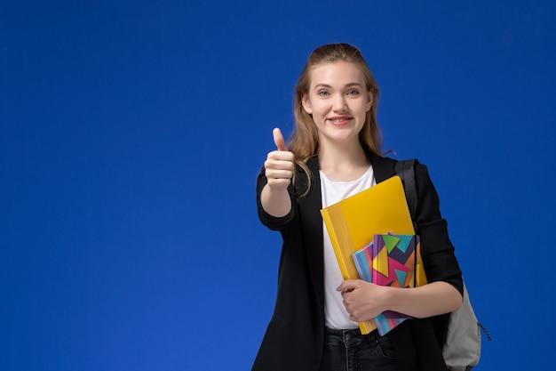 Aluna com uma jaqueta preta usando uma mochila segurando arquivos com cadernos e sorrindo na parede azul.