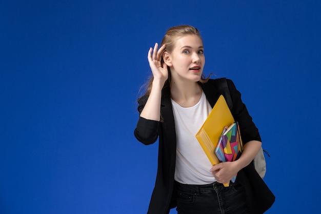 Aluna com uma jaqueta preta usando uma mochila segurando arquivos com cadernos, tentando ouvir na parede azul, aula de universidade