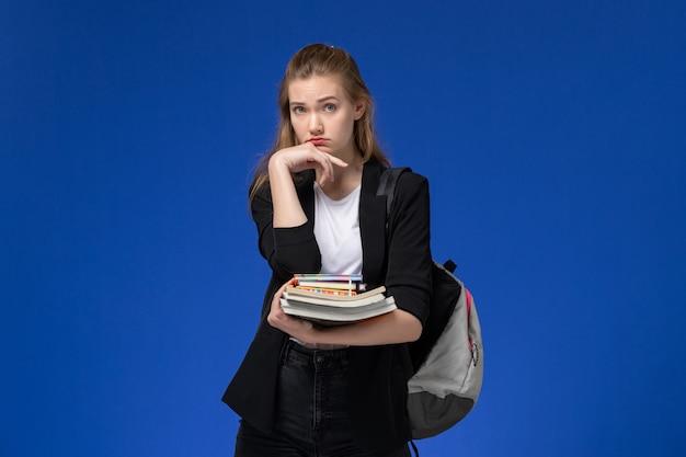 Aluna com uma jaqueta preta usando uma mochila segurando livros na parede azul-clara, desenho da faculdade de arte