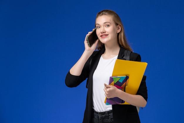 Aluna com uma jaqueta preta usando uma mochila segurando um arquivo e um caderno falando ao telefone na parede azul.