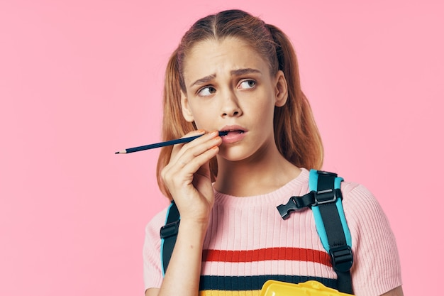 Aluna com uma mochila segura uma caneta e olha para o lado em um fundo rosa