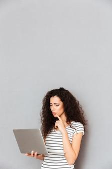 Aluna concentrada com cabelo encaracolado em pé com o notebook nas mãos, estudando muito ou lendo ebook interessante sobre parede cinza