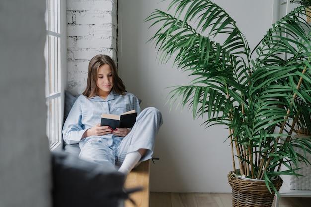 Aluna concentrada grave focada no livro, usa pijama, senta-se no peitoril da janela na sala acolhedora