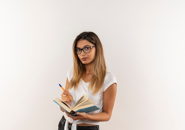 Aluna confiante jovem e bonita segurando uma caneta e um livro aberto isolado no branco com espaço de cópia