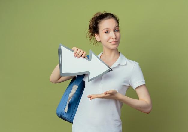 Aluna confiante jovem e bonita usando uma bolsa de costas segurando a marca de seta que está apontando para o lado e apontando com a mão para ela isolada no fundo verde oliva