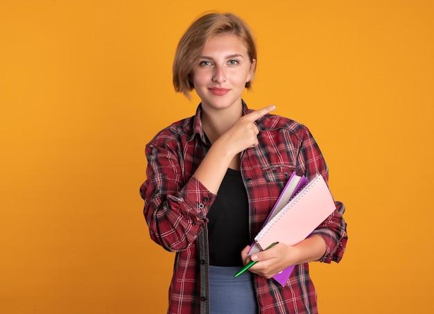 Aluna confiante jovem eslava segurando o caderno e as pontas do caderno ao lado