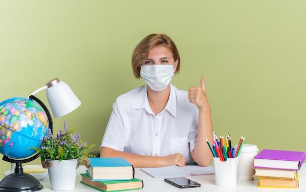 Aluna confiante jovem loira usando máscara protetora sentada na mesa com as ferramentas da escola, olhando para a câmera aparecendo o polegar isolado na parede verde oliva