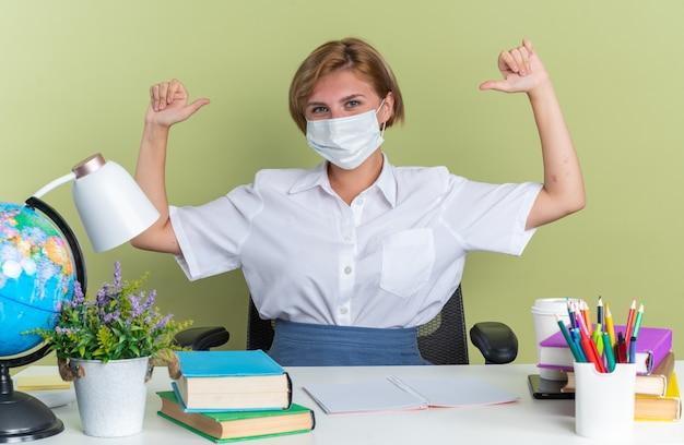 Aluna confiante jovem loira usando máscara protetora, sentada na mesa com ferramentas escolares, olhando para a câmera, apontando para ela mesma, isolada na parede verde oliva