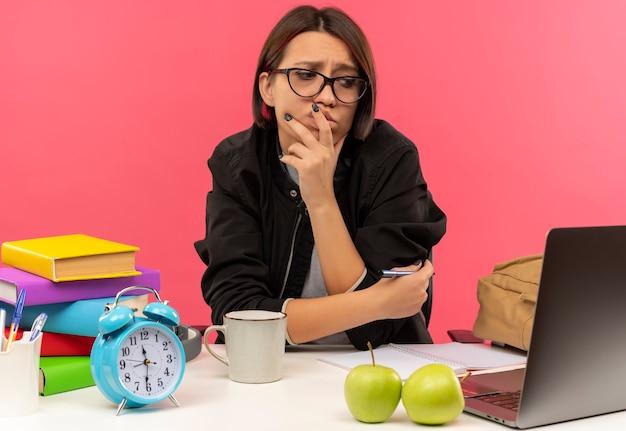 Aluna confusa de óculos sentada na mesa olhando para o lado colocando a mão no queixo e lábios e outra no braço com uma caneta fazendo lição de casa isolada em rosa