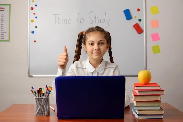 Aluna da escola pequena trabalhando no laptop na sala de aula, mostrando os polegares para cima, feliz por usar as tecnologias no estudo